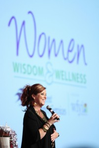 Kelly Swanson  with microphone being funny women's health weight loss, womens speakers, speak well being